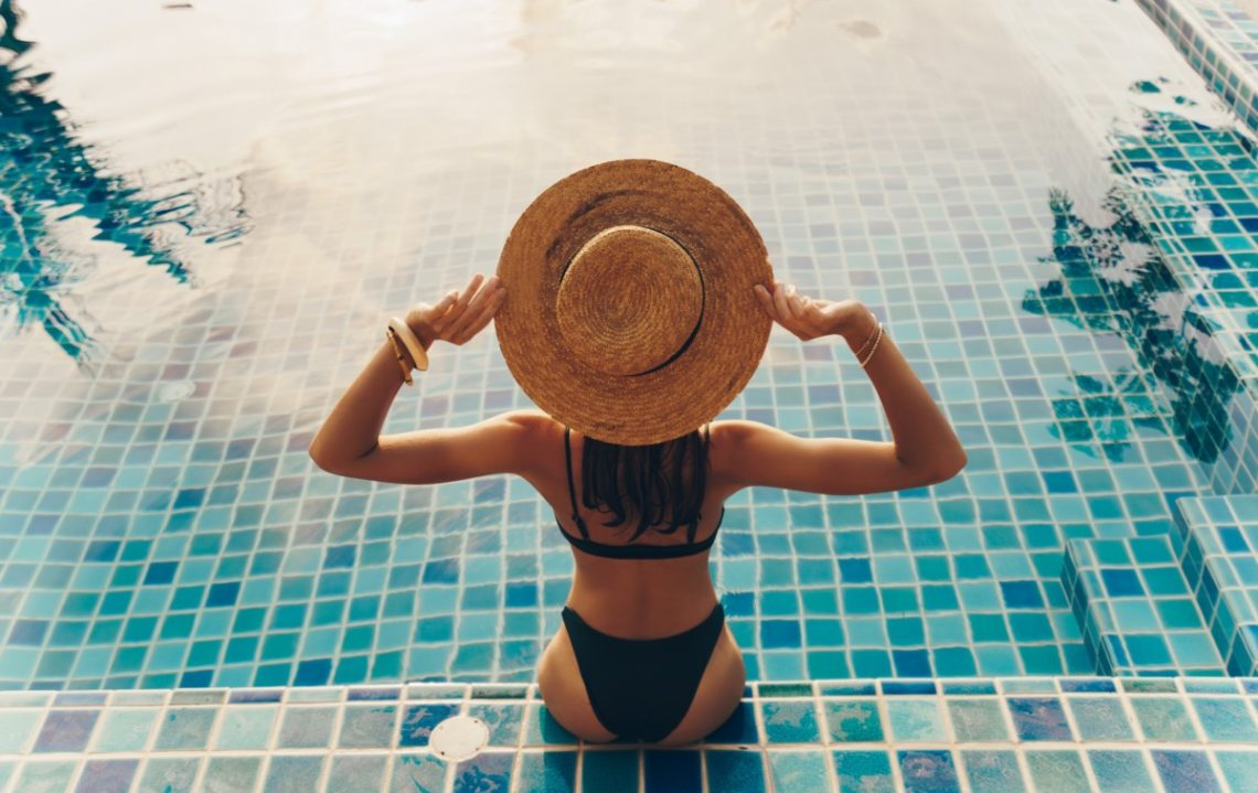 back-view-of-graceful-woman-in-swimsuit-and-hat-sitting-near-the-pool-1140x719 Le summer body sans salle de sport c'est possible !