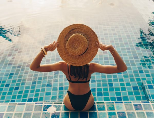 back-view-of-graceful-woman-in-swimsuit-and-hat-sitting-near-the-pool-600x460 Le summer body sans salle de sport c'est possible !
